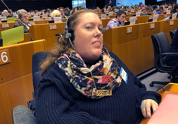 Karolina Celinska sitter i parlamentssalen med hörlurar på.