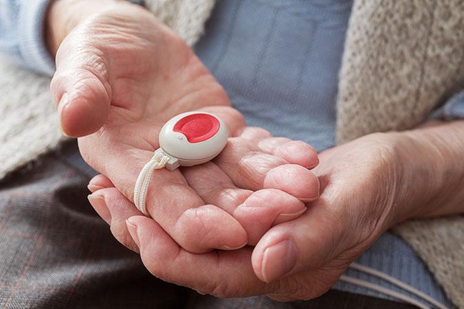 En hand hos en äldre person håller en larmknapp till trygghetslarmet.