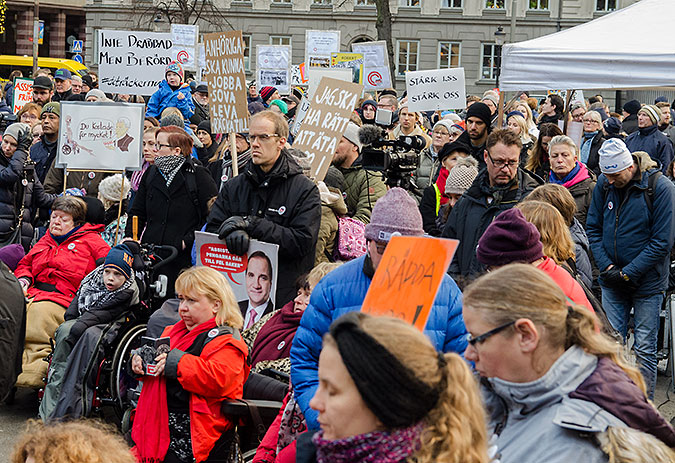 Många människor som står med plakat och protesterar.