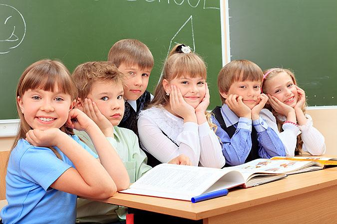 Glada skolbarn i 10-årsåldern samlas runt en bänk med skolböcker.