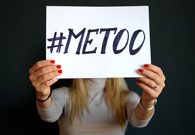 En person håller upp en skylt framför ansiktet där det står #metoo.