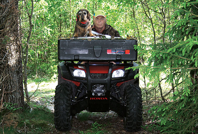 En bild på en man som kör fyrhjuling i skogen. På fordonet sitter även en hund.