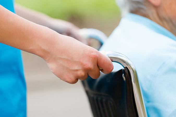 En äldre person blir körd i rullstol av en yngre.