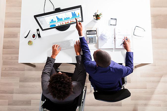 Två personer jobbar framför en dator. En av dem sitter i rullstol. bilden är tagen uppifrån.
