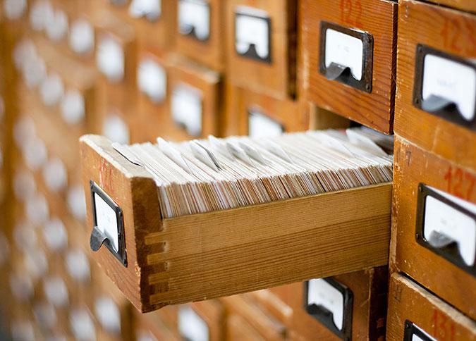 En utdragen arkivskåpslåda i trä med massor av arkivkort i. Lådan är en del av ett större skåp med många likadana lådor.
