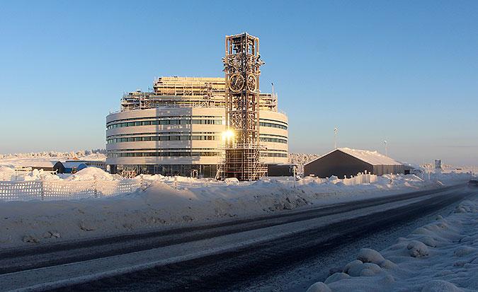 Det runda stadshuset i Kiruna täcks på den här bilden fortfarande av några byggställningar på taket. På marken ligger snö, himlen är blå. Solen reflekterar i klocktornet som står framför huset.