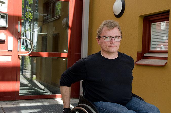 Man i rullstol framför en dörr där det står Gävle tingsrätt.