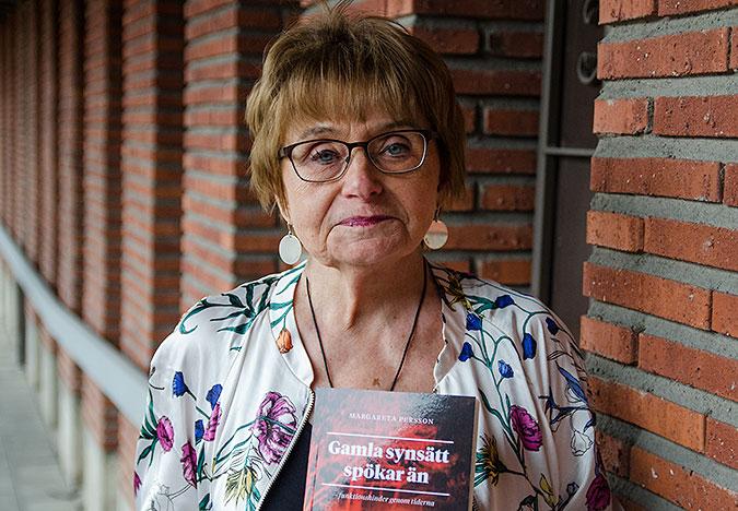 Bild där Margarete Persson står vid en rödorange tegelvägg och håller i sin bok.