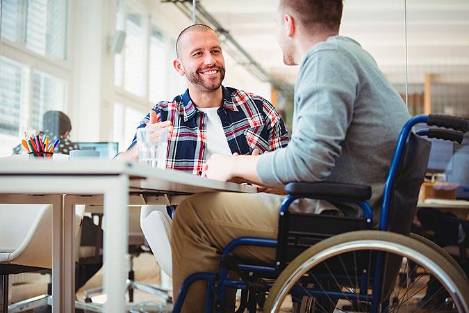 Två personer sitter vid ett bord på ett kontor.De ser glada ut. En av dem använder rullstol.