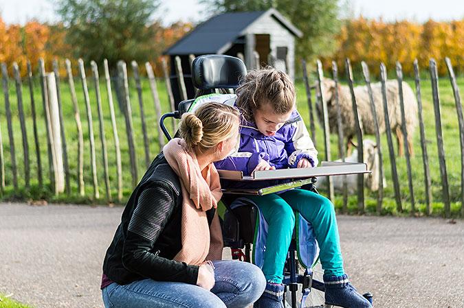 Ett barn i rullstol och en kvinna som sitter på huk bredvid. I abkrgunden står får bakom ett staket.