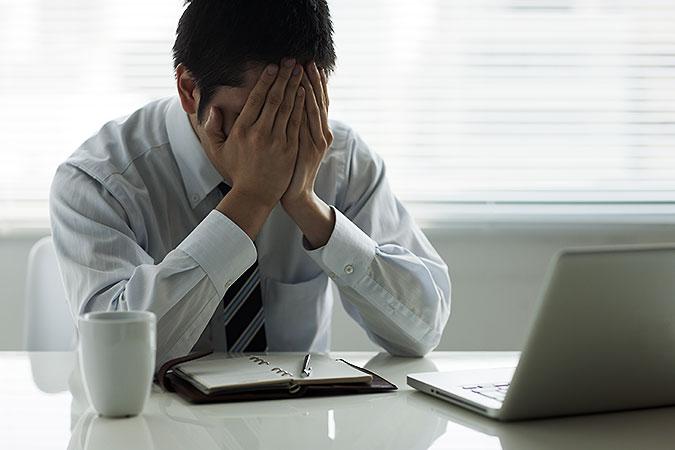 En man i vit skjorta sitter vid skrivbordet med en dator, kalendeer och kaffekopp. Anhåller händerna för ansiktet och ser ganska uppgiven ut.