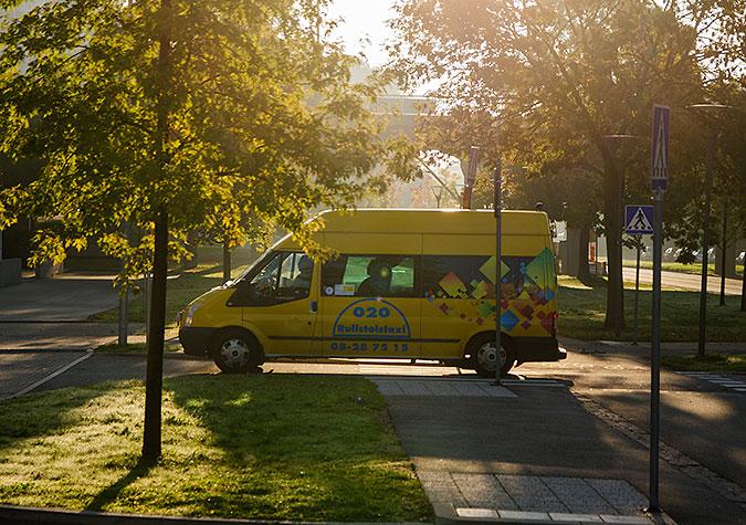 En gul färdtjäsntbuss kör på en väg bland träd.