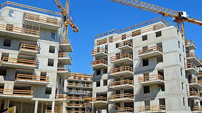 En byggarbetsplats med betongskelett till hus och gula byggkranar.