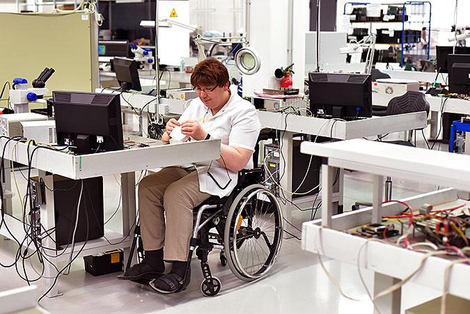 En man sitter i rullstol och arbetar vid en bänk i nån slags teknisk produktion eller repartionsverkstad.